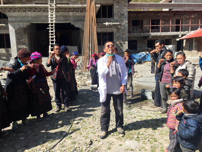 Dentist Phurbu teaching villagers how to brush their teeth