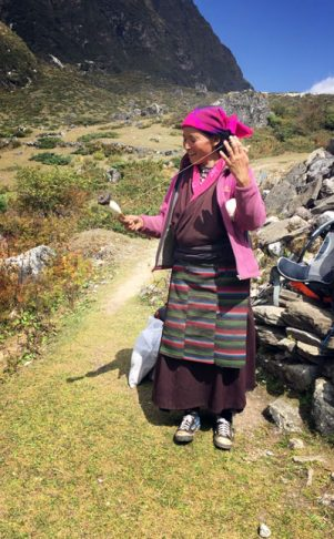 Tibetan woman spinning as she walks between villages along our route.